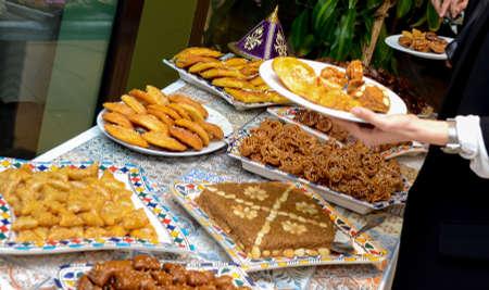 Moroccan buffet, traditional Moroccan food, tagine, chebakia, and Arabic sweets.
