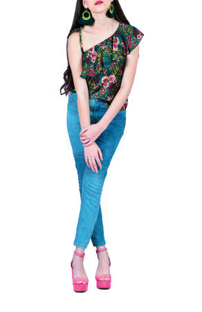 Fashion model wearing jeans with red shoes. A girl in a photography studio.