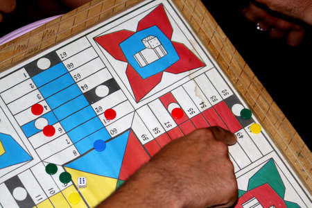 MAN Hand throwing two dices playing Parcheesi, Parchis game over game board