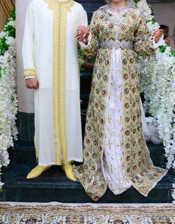 Moroccan Wedding. The groom is wearing Moroccan jellaba. He holds in the hands of the bride who wears the MOROCCAN caftan