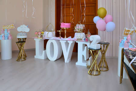 Delicious sweet buffet with cake. Candy Bar. Design of balloons. Many pink and golden balloons decoration wall