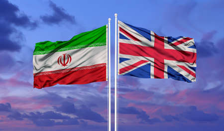 Iran and United Kingdom two flags on flagpoles and blue cloudy sky
