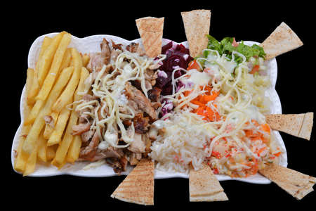 Shawarma dish with french fries. Boiled vegetables and rice on a black background. Street food concept Imagens