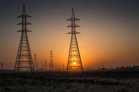 iraqi: Sunsrise in Iraqi desert where the huge power line towers Stock Photo