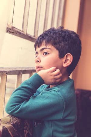 looking through window: Boy looking through window inside house in Iraq Stock Photo