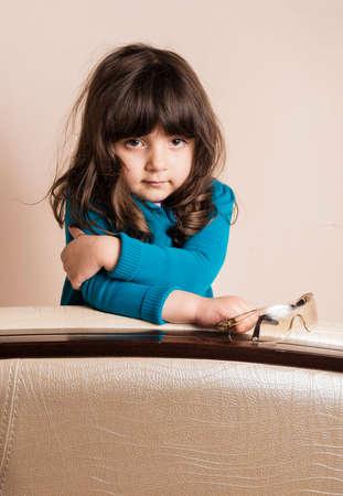 samll: Samll girl leaning on cushion arm inside studio