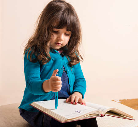 samll: Samll girl inside studio with red copybook and blue pen in hand in hand
