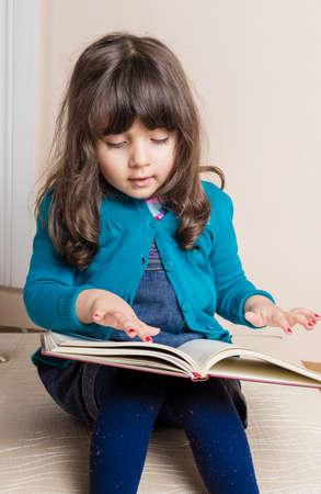 samll: Samll girl inside studio with red copybook in hand