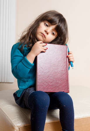 copybook: Samll girl inside studio with red copybook in hand