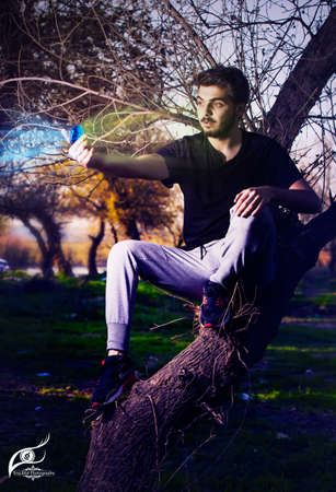 grabing: Fantasy scene of young boy sitting on tree using polarizer filter to convert light color Stock Photo