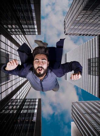 levitation: Levitation scene of boy inside narrow space between high building Stock Photo