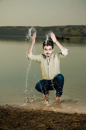 iraqi: Caucasian boy playing with water splash in Iraqi countryside Iraqi countryside