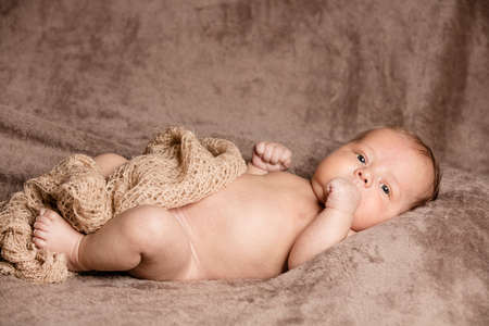 New Born Baby playing inside burlap fabric