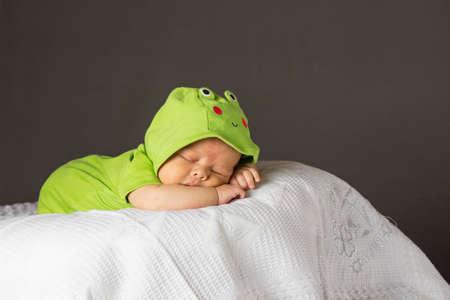 white blanket: New Born Baby Sleeping wth green dress on white blanket Stock Photo