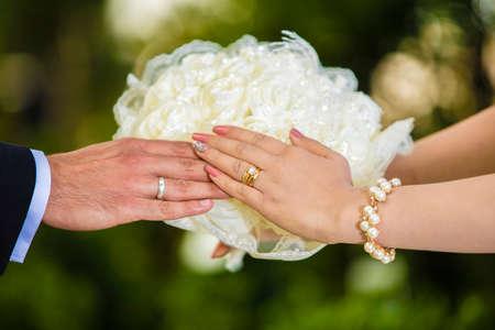 Nevěsta a ženich ruce drží svatební květinu s thrm manželství kroužky v ruce