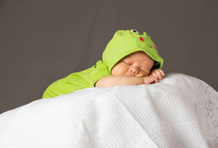 New Born Baby Sleeping wth green dress on white blanket Reklamní fotografie
