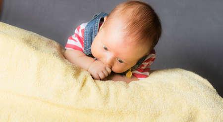 Nově narozené dítě na jeho towl isloated uvnitř studio Reklamní fotografie