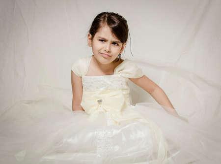 Malá dívka v svatební šaty sedí osaměle v ateliéru