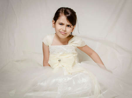 Small girl in bridal dress sitting isolated inside studio