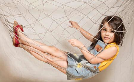 Malá dívka pozastaven uvnitř síti izolované v pozadí Reklamní fotografie