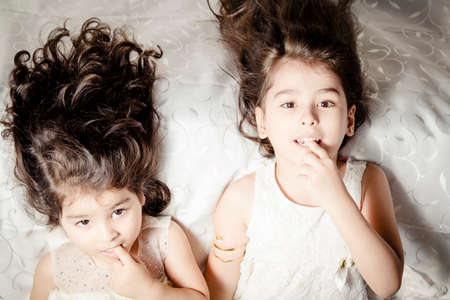 Mladší sestra na Silky posteli uvnitř ložnice Reklamní fotografie
