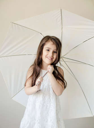 Small girl with white umbrella ioslated inside house