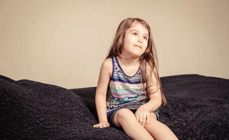 Malá bruneta dívky uvnitř ložnice přes tmavou tkaninu