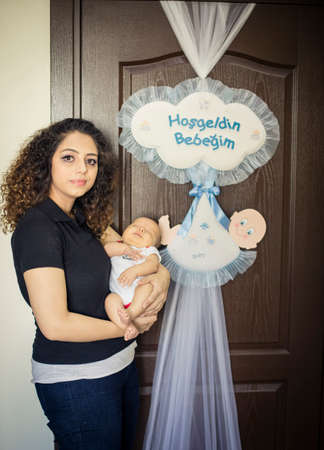 Mom with her newborn baby standing in front of door with ornamet text in turkish says Welcome my new baby Reklamní fotografie