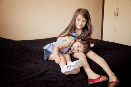 Dvě malé sestry sedící uvnitř ložnice přes tmavou tkaninu Reklamní fotografie