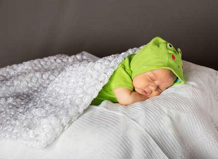 New Born Baby Spací wth zelených šatech na bílou přikrývkou