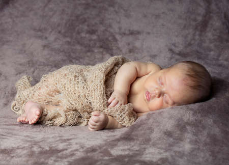 Nové narozené dítě spí s hnědou látkou
