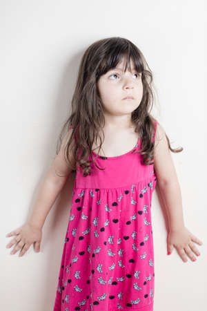 Small girl in strange pose wearing pink dress