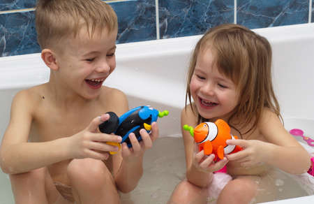 Boy And Girl Are Plaing In Bath With Toy Fish Stock Photo, Picture ...