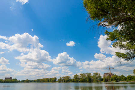 puffy: Clear lake reflecting blue sky with puffy white clouds in bright sunny day Stock Photo