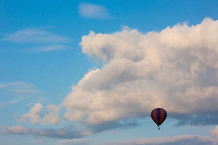 air baloon: Lonely air baloon flying in front of white puffy clouds