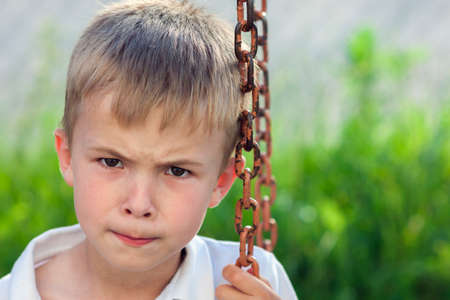 dissatisfied: Portrait of a little displeased and dissatisfied boy with golden blonde straw hair in sunny summer day on green blurred background Stock Photo