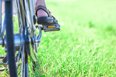 bicycle pedal: Womans foot on bicycle pedal on green grass closeup Stock Photo