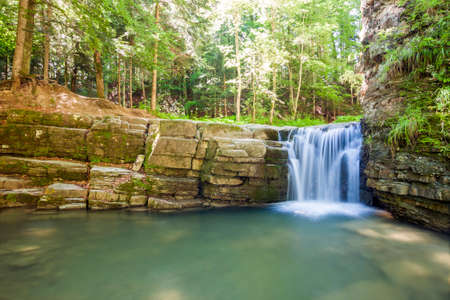 slow motion: Little waterfall in mountain forest with silky foaming water