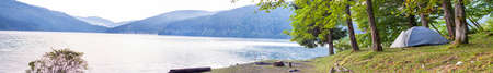 Camping tent on the bank of a lake panorama