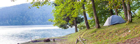 campsite: Camping tent on the bank of a lake panorama