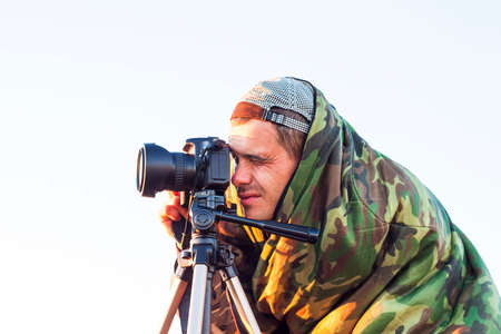 photojournalist: Closeup of a camouflaged paparazzi photographer  taking picture with a camera on a tripod Stock Photo