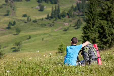 Lonely hiker tourist enjoing mounain view in sunny summer day Stock Photo