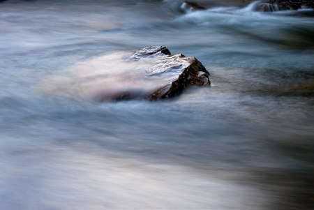 Stone in a river with fast moving water around Stock Photo