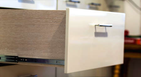 A detail close up shot of a laminate stylish kitchen drawer