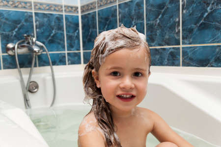 bath: Cute little girl washes her hair. Clean kid after shower. Children hygiene. Child taking bath. Little baby in a kitchen sink washing hair with shampoo and soap. Water fun for kids. Hygiene and skin care for children. Bath room interior