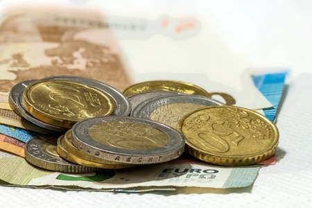 Money euro coins and banknotes stacked on each other in different positions. Money concept. Detail of Euro currency on the desk. Stock Photo