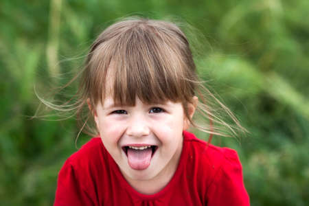 Smiling little girl shows tongue. Young cute little girl gesturing with her mouth.