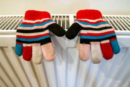 Childs knitted gloves drying on heating radiator after winter day outside Stock Photo