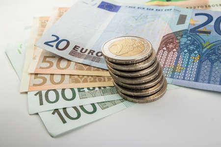 banconote euro: Le monete e le banconote in euro moneta impilate l'una sull'altra in posizioni diverse. Concetto di denaro. Dettaglio della valuta euro sulla scrivania.