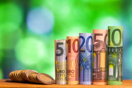 Five, ten, twenty, fifty and one hundred euro rolled bills banknotes, with euro coins on green blurred bokeh background.